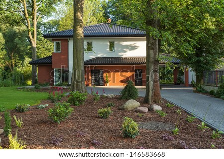A modern house surrounded by trees - stock photo