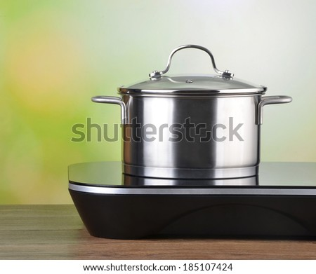 A modern induction stove and a saucepan - stock photo