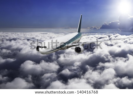 A modern jet airliner flies at high altitude over a cloudy sky.