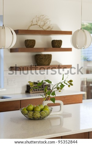 A modern kitchen shown with solid counter tops and wood shelving. - stock photo