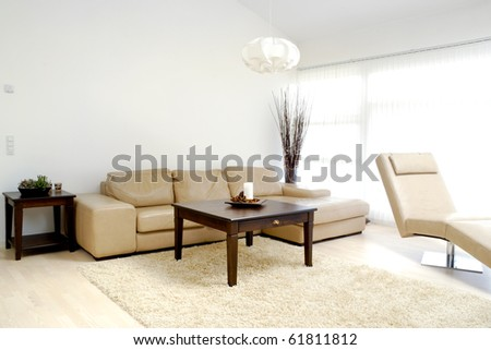 A modern living room with table, sofa and armchair. - stock photo