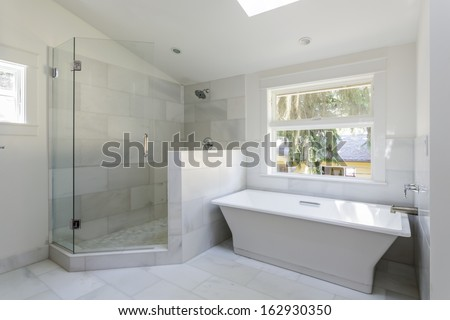 A modern, marble tile bathroom with an open walk-in shower and bathtub during daytime. Also shows a view at a yellow house and tree branch.