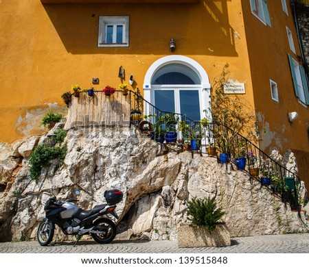 A modern motorcycle parked by an old stone staircase leading to an orange stucco villa - stock photo