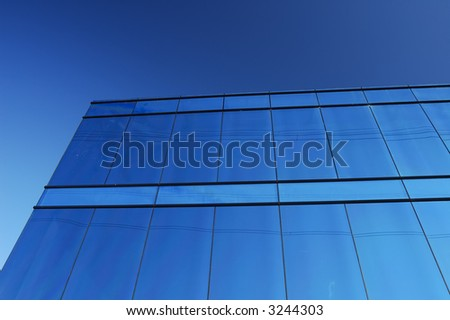 A modern office block with a glass facade reflects the clear blue of a cloudless sky, with some power lines.