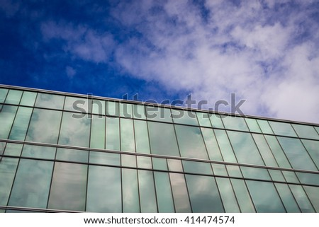 a modern style office building with blue sky and cloud in the background