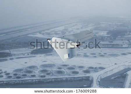 A modern style UCAV, unmanned combat air vehicle flys over frozen land looking for enemy targets. UCAVs are armed drones. (Artists impression - computer drawing) - stock photo