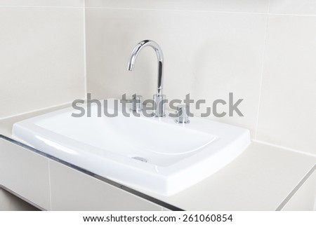 a modern washstand with shiny faucet and basin - stock photo