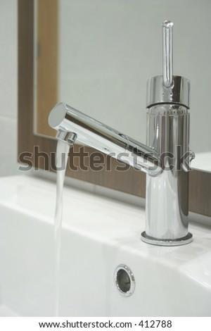 A modern water tap with water coming down of it.