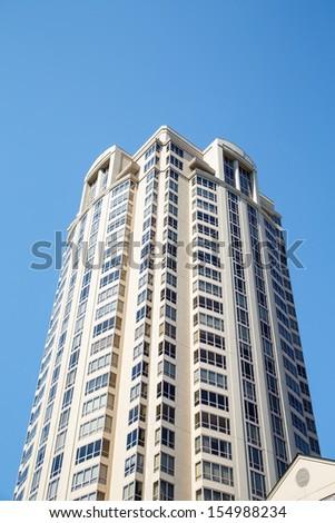 A modern white condominium tower under clear blue skies - stock photo