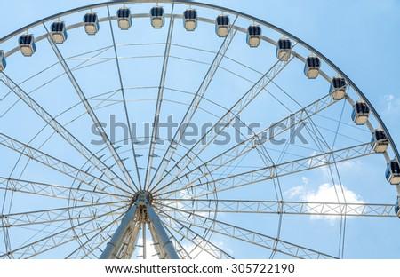 A modern white Ferris wheel against brilliant blue sky - stock photo