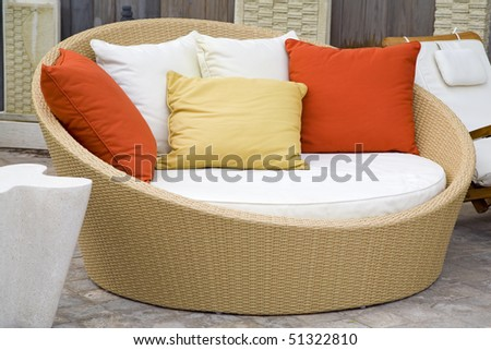 A modern wicker garden sofa in the home garden.
