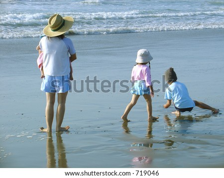 A mom, a baby, and two small children enjoy a day at the sea side.