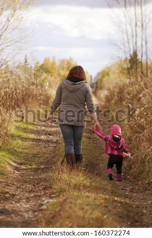 A mom and her toddler daughter walking down an old country road pathway surrounded by long tall grasses. - stock photo
