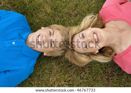 A mom and teenage son lying head to head in the grass