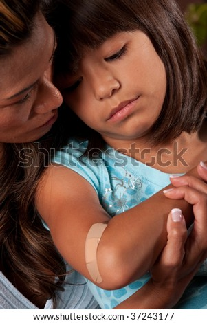 a mom comforts her young daughter who has a wound - stock photo