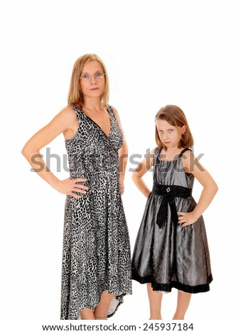 A mom with her young daughter standing in dresses for white background having trouble with each other.  - stock photo