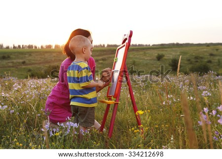 a Mom with son draw on nature , beautiful sunset - stock photo