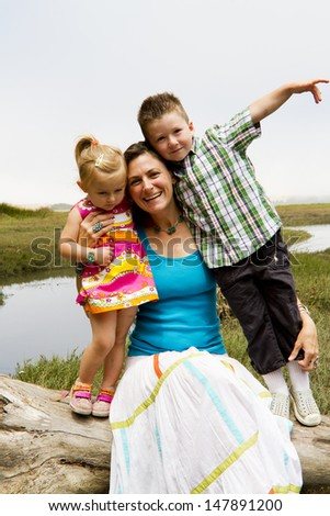 A mom with young children enjoys the outdoors together. - stock photo