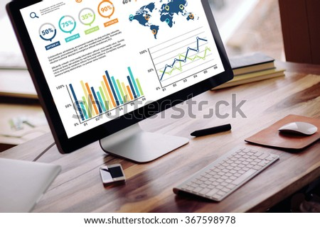 A monitor showing business graphic charts on a work station desk. - stock photo