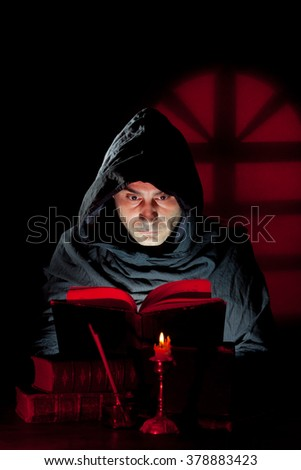 A Monk read mystical occult book in the dark