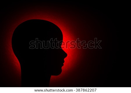 A monochromatic silhouetted side profile of a female mannequin head again a black background with red halo