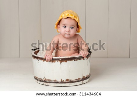 A 6 month old baby girl wearing a yellow knitted hat and sitting in a vintage wooden bucket. Shot in the studio on white hardwood floors and a white wooden backdrop. - stock photo