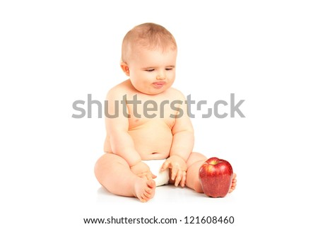 A 9 months old baby boy sitting and looking at a red apple isolated on white background - stock photo