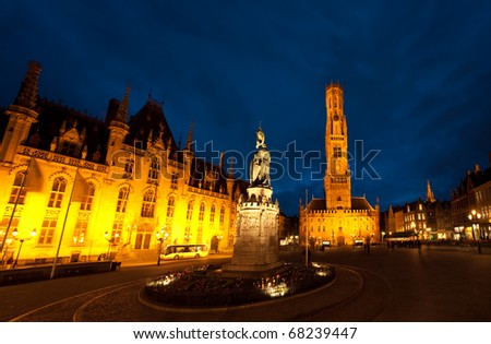 A moody dark blue night sky above Grote Markt and the provincial courthouse and clock tower in the city center of Bruges, Belgium - stock photo