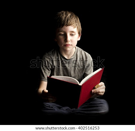 A moody studio shot of a boy and his book