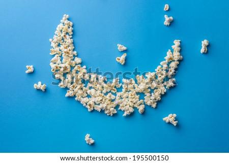 A moon shaped arrangement by pop-corns on blue background, defocused - stock photo