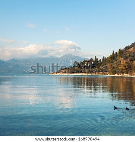 a morning at Lago di Garda lake near resort Malcesine with mountains as a background  - stock photo