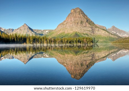 A morning reflection on Two Medicine Lake in Glacier National Park, Montana. - stock photo