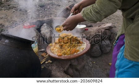 A Moroccan woman cooking a traditional tagine meal with carrots, potatoes, green chili and other vegetables, in the Atlas mountains of Morocco, on May 13th, 2014.  - stock photo