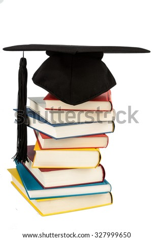 a mortar board on a pile of books, symbolic photograph of education and competence - stock photo