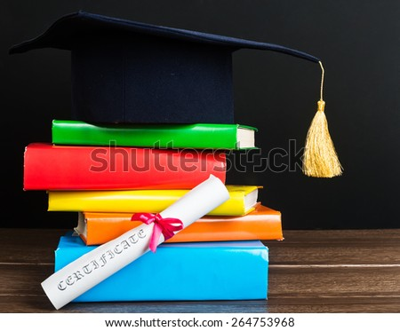 A mortarboard and graduation scroll, tied with red ribbon, on a stack of books  - stock photo