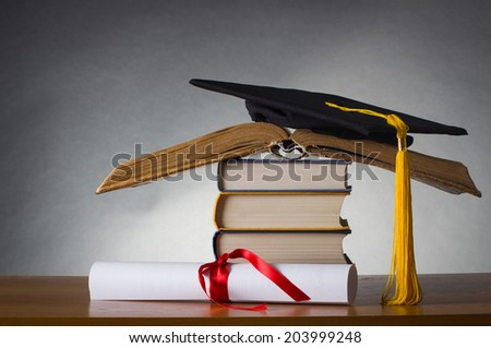 A mortarboard and graduation scroll, tied with red ribbon, on a stack of old battered book - stock photo