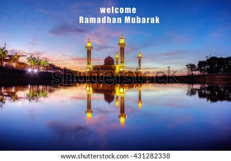 """A mosque during sunrise with wording """"Welcome Ramadhan"""" - stock photo"""