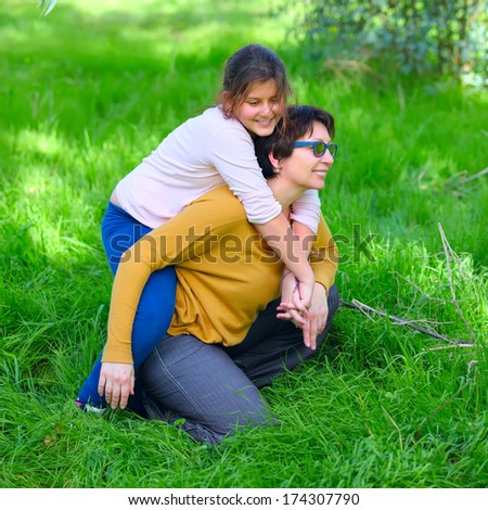 a mother and a daughter on the green grass in a park