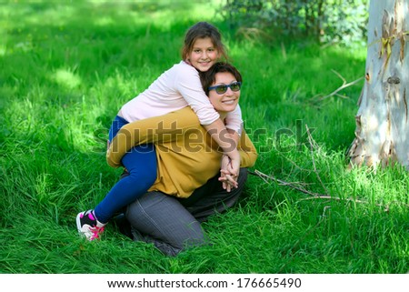 a mother and a daughter on the green grass in a park  - stock photo