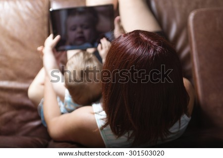 A mother and baby are looking to play and read tablet computer on the couch at home - stock photo