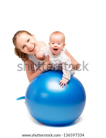 A mother and baby doing gymnastic exercises on the ball - stock photo