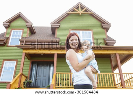 A Mother and baby in front of the house - stock photo