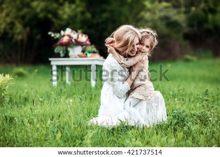 A mother and child cuddling and having fun in nature. The concept of life values and happiness - stock photo