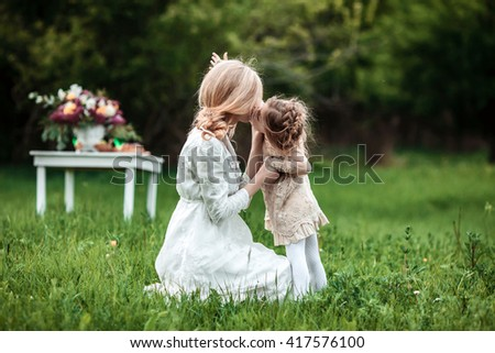 A mother and child in nature. Little girl kisses her mom. The concept of life values, peace, security and love - stock photo