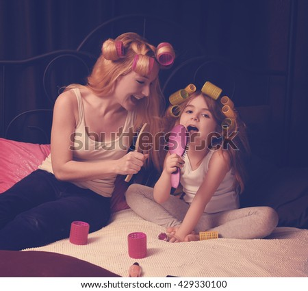 A mother and daughter are together on a bed with beauty supplies singing into a brush for a love, parenthood or family concept - stock photo
