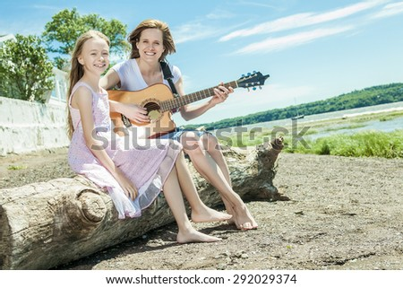 A mother and daughter on the side of the beach play guitar - stock photo