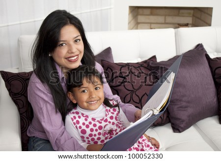 A mother and daughter reading book stories - stock photo