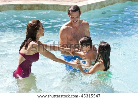 A mother and father having fun on vacation playing with their children on their shoulders in a swimming pool - stock photo