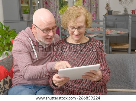 a mother and her adult son looking at a digital tablet on a sofa - stock photo