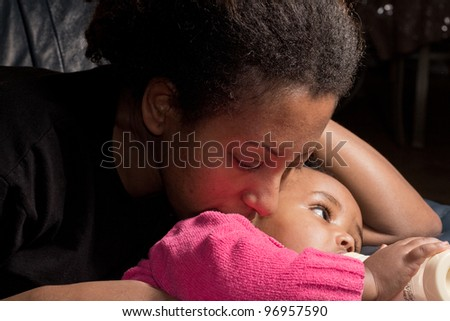 A mother and her baby girl who is drinking her bottle of milk - stock photo
